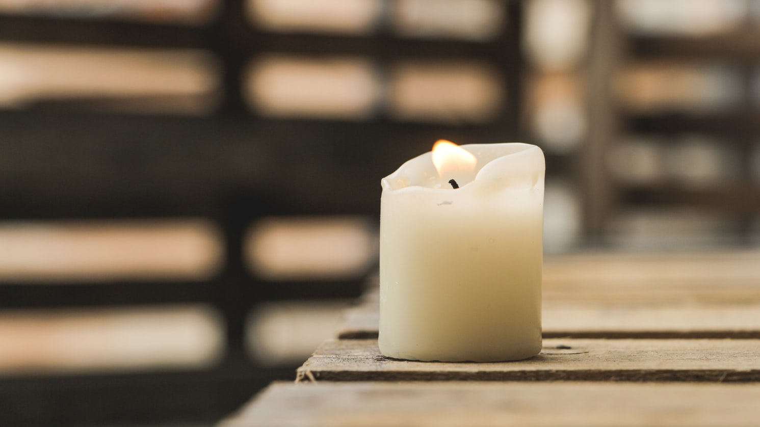 a candle is burning and sat on a wooden bench outside in a close up shot