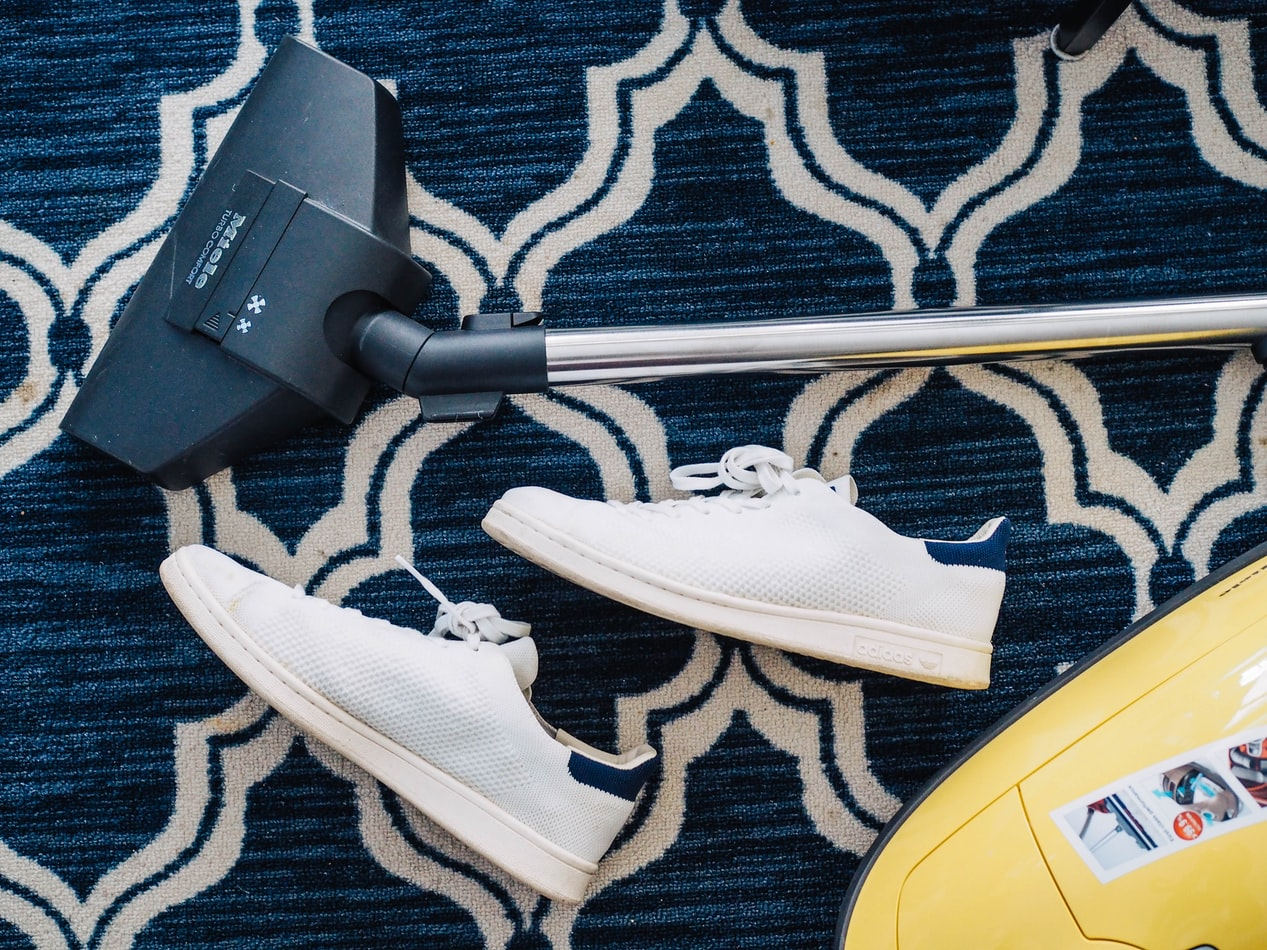 trainers on the floor next to a hoover used to remove candle wax from the printed rug