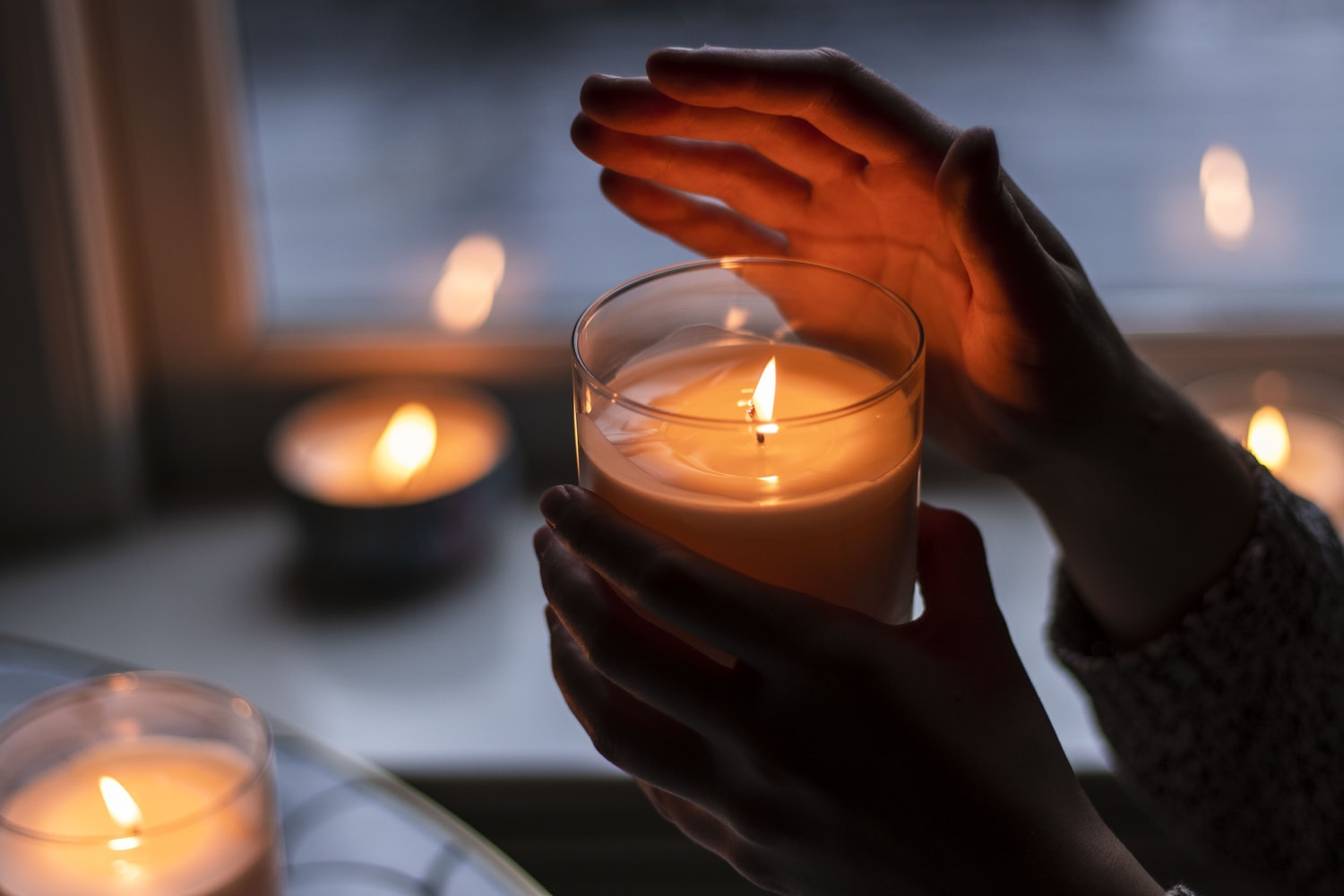 a person holds a candle up to the camera in a dark room with their hand over the flame