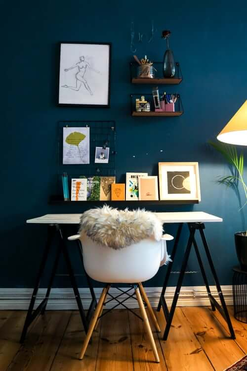 a dark navy wall with a home office desk in front with books and shelves and wooden chair
