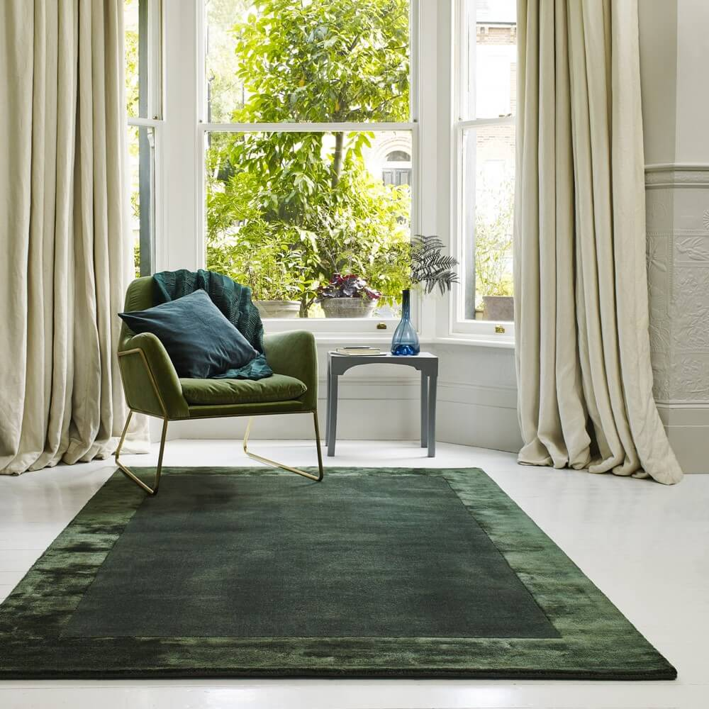 a neutral room with a dark green wool rug and suede green chair