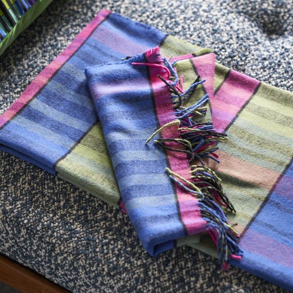 brushed cotton throw in cobalt striped folded on a bed