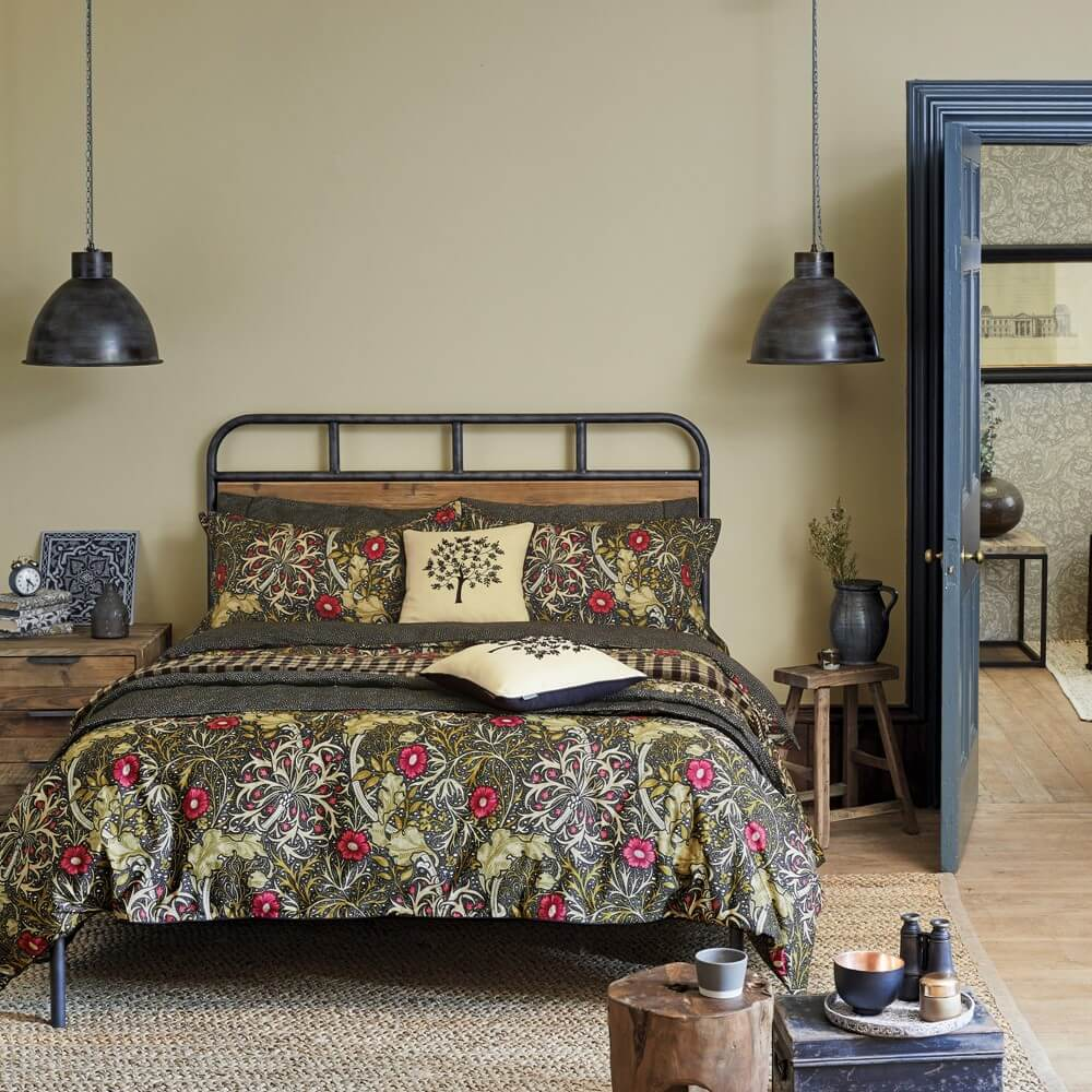 autumnal bedding by william morris seaweed print on a bed in a bedroom