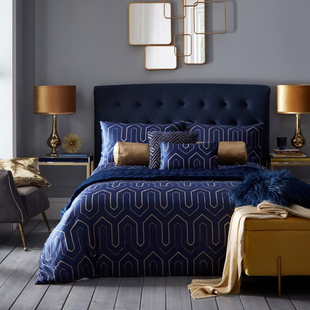 dark blue bedding and embroidered geometric shapes on a bedding set in a modern bedroom