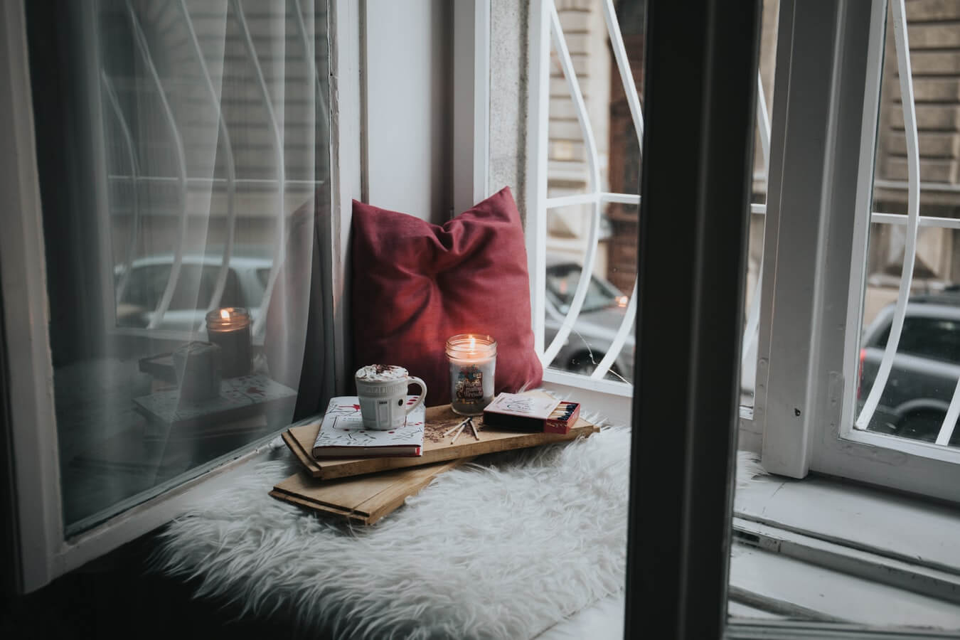 an autumnal interior trends image of cosy and dark reading corner on a windowsill with candle and red cushion