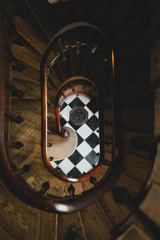 a set of dark wooden spiral stairways taken from above with a checkered floor below