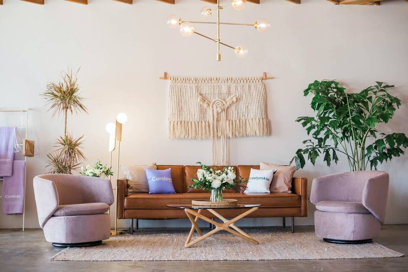 a cosy neutral room with jute rug, pale pink chairs and brown leather