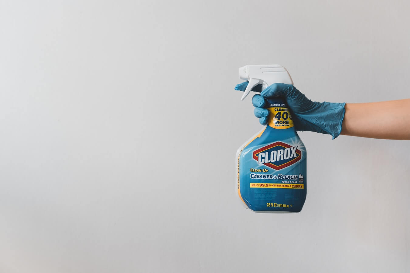 a spray bottle being held by a gloved hand showing how to remove coffee stains