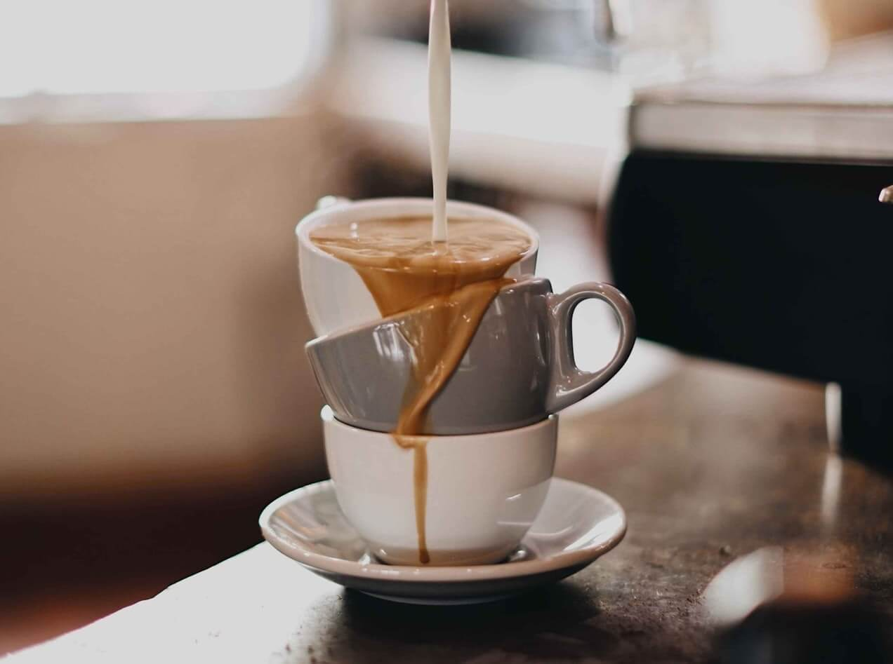coffee cups piled on top of each other with coffee spilling over the side