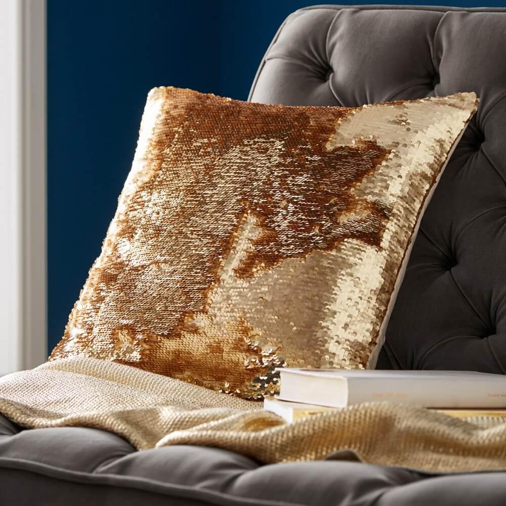 a gold sequin cushion on a grey sofa