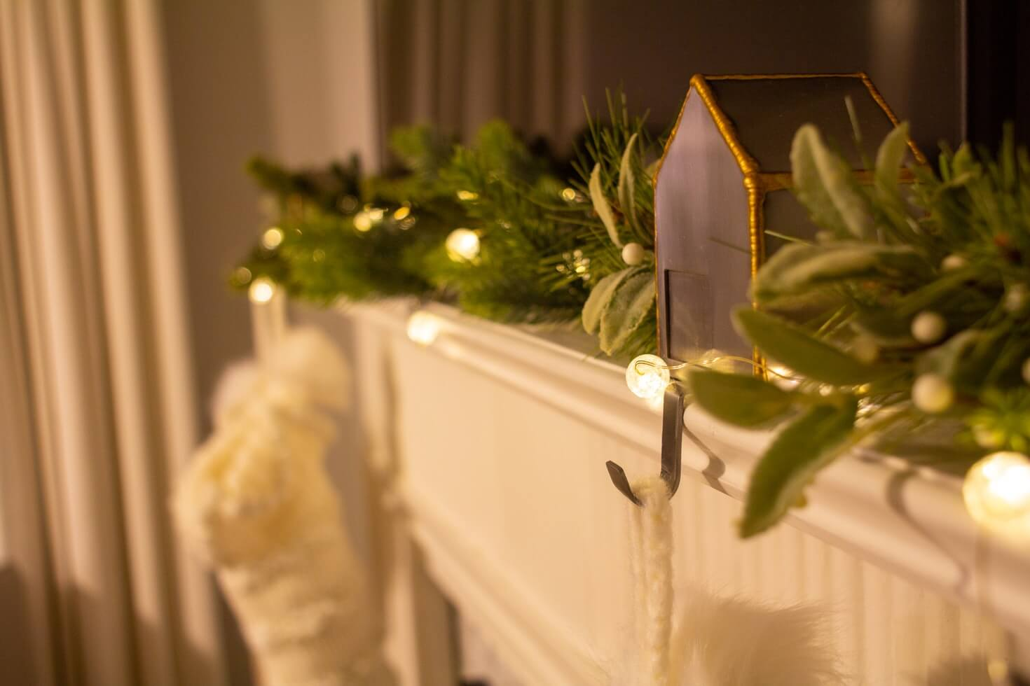 a mantlepiece decorated for festive hosting with evergreen and stockings