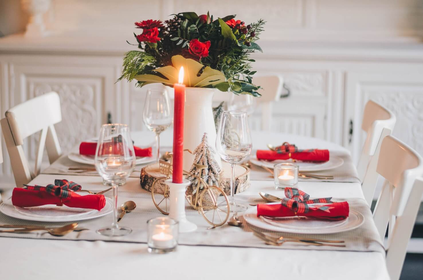 a table set with red napkins, candels and roses for festive hosting