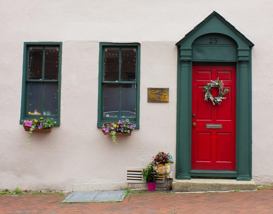 a red festive front door with floral wreaths on the door and windows